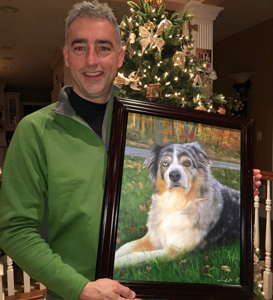 A man holds a custom painting of a beloved pet in a beautiful dark wood frame.